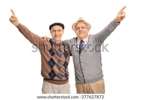 Studio shot of two old friends celebrating together and pointing up with their fingers isolated on white background