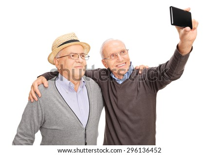 Studio shot of two senior men taking a selfie with cell phone and smiling isolated on white background - stock photo