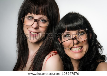 Studio shot of two smiling girls with glasses on gray background - stock photo