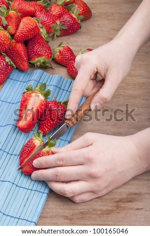 studio-shot of woman`s hands cutting a fresh strawberry in halves. - stock photo
