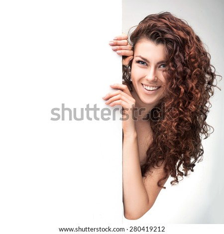 studio shot of woman with brown curly hair holding white signboard isolated  - stock photo