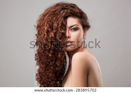 studio shot of woman with healthy brown curly hair isolated over grey background