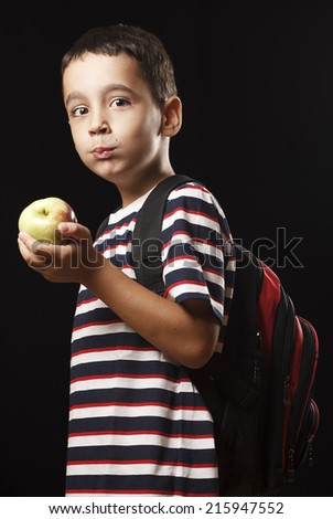 Studio shot of 5 years old preschooler who is eating apple. - stock photo
