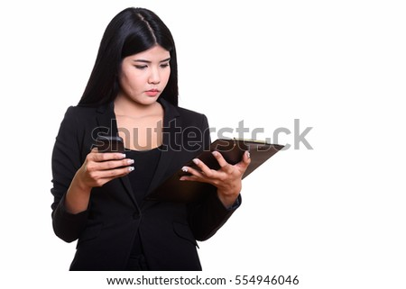 Studio shot of young Asian businesswoman reading on clipboard while holding mobile phone isolated against white background