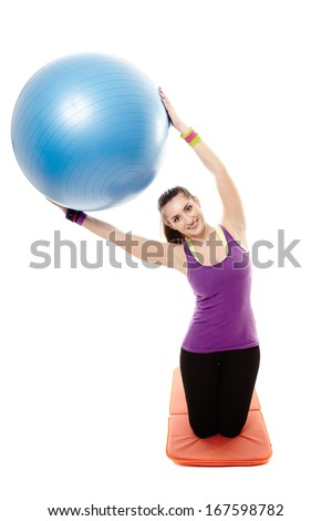 Studio shot of young athletic woman sitting on the floor and stretching with a ball, isolated over white background