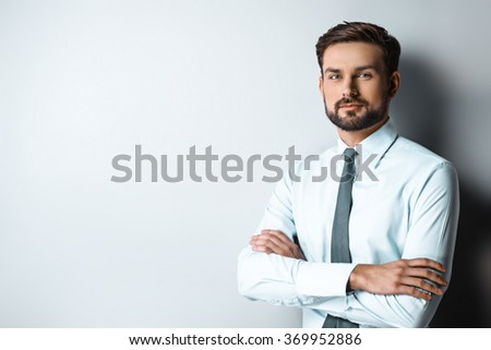 Studio shot of young attractive businessman. Businessman thoughtfully looking at camera - stock photo