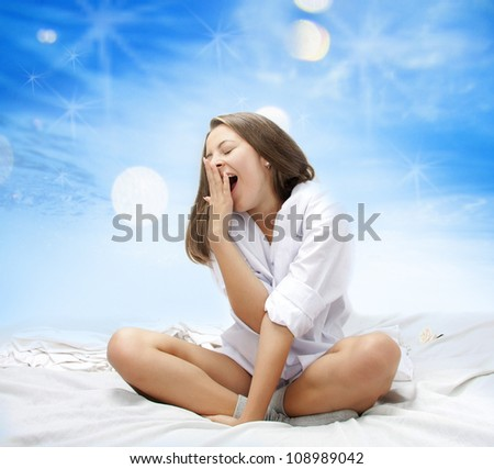 studio shot of young attractive woman yawning in bed - stock photo