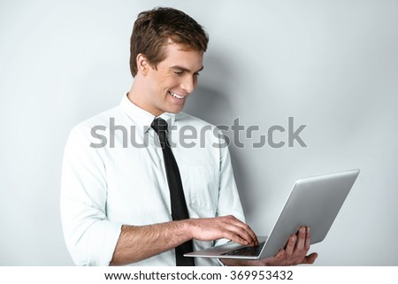 Studio shot of young handsome businessman. Businessman smiling and using laptop