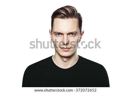 Studio shot of young handsome man. He is looking to the camera, he is wearing a black T-shirt. - stock photo