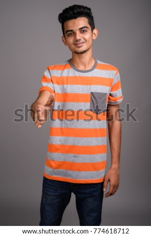 Studio shot of young Indian man against gray background