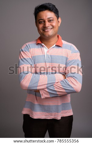 Studio shot of young Indian man wearing long sleeve striped polo shirt against gray background