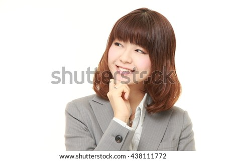 studio shot of young Japanese businesswoman wearing gray suits dreaming at her future - stock photo