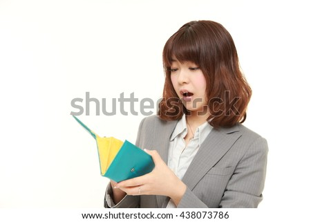 studio shot of young Japanese businesswoman wearing gray suits looking her empty wallet - stock photo