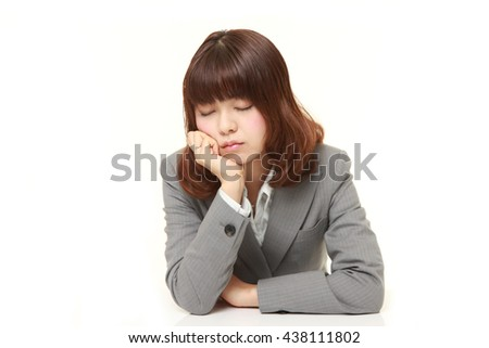 studio shot of young Japanese businesswoman wearing gray suits sleeping on the desk - stock photo