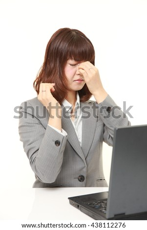 studio shot of young Japanese businesswoman wearing gray suits suffers from Asthenopia - stock photo