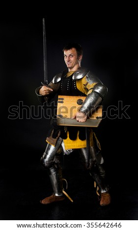 Studio shot of young man dressed as medieval knight with a sword carrying a treasure chest - stock photo
