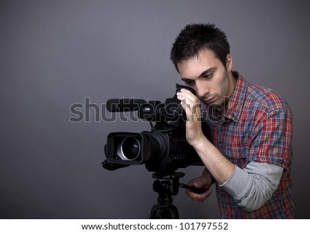 Studio shot of young man with video camcorder on gray background with copy space - stock photo