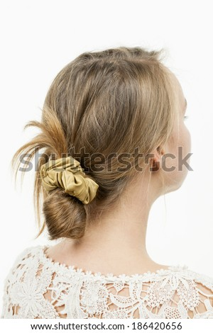 Studio shot of young woman with casual messy chignon hairstyle - stock photo