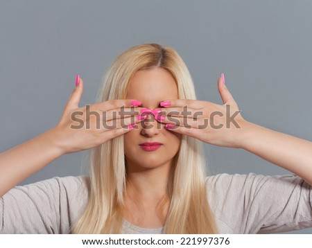 Studio shot of young woman with her hands covering eyes. - stock photo