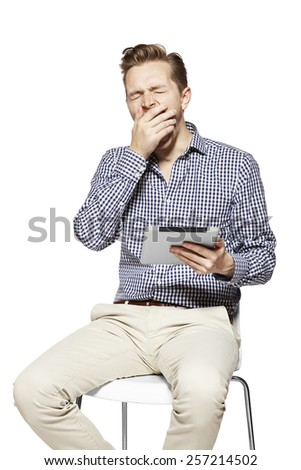 Studio shot of young yawning man. Working on tablet.  - stock photo