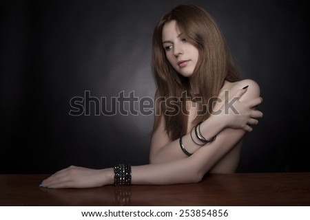 Studio shot. Portrait of fashionable model with long curly natural ginger red hair and make-up posing over black background.  - stock photo