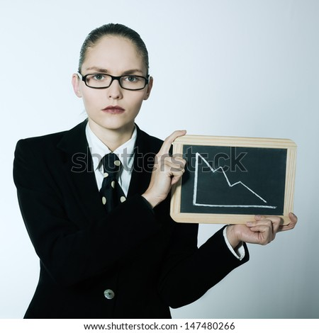 studio shot portrait of one business woman showing blackboard with deacreasing curve - stock photo