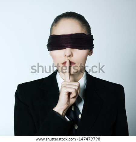 studio shot portrait  young blindfold business woman hushing finger on lips