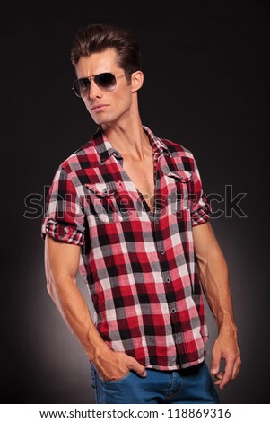studio side view of a handsome young male model wearing jeans , shirt and sunglasses - stock photo