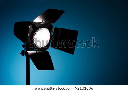 Studio spot light on blue background - stock photo