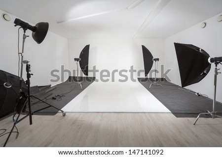 Studio with photographic equipment and a white backdrop - stock photo