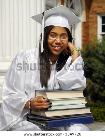Studious, smiling graduate resting on the school steps with a lap full of books. - stock photo