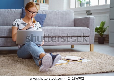 Studious young woman working at home sitting on the floor in the living room with a laptop and class notes in binders studying for university