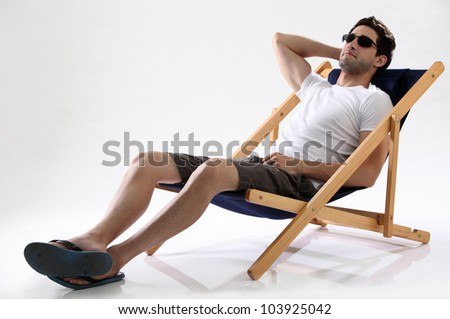 studo shot of man resting on a chair - stock photo