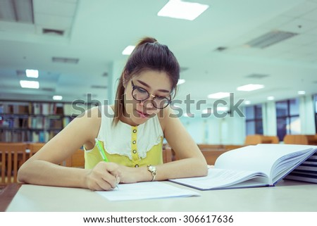 study education, woman writing on a paper, working women - stock photo