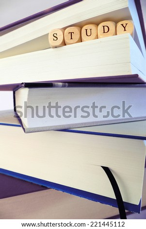 Study message written in wooden blocks between pages of a book, stack of books, symbol, concept - stock photo