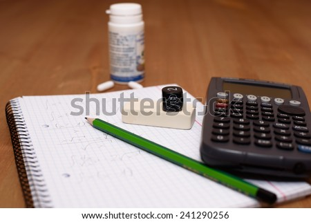 study place with calculator and painkillers in background - stock photo