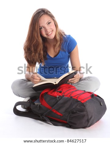 Study time for beautiful high school teenage student girl reading education book sitting cross legged on floor, with school rucksack wearing blue t-shirt, jeans and red sneakers. - stock photo