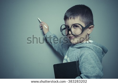 study, young student writing on a blackboard school with a book in hand and big glasses