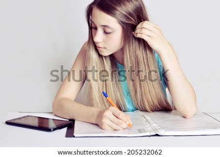 Studying cheerful  teenager girl with Digital Tablet . Cheerful  teenager girl reading her book for school and making notes. - stock photo