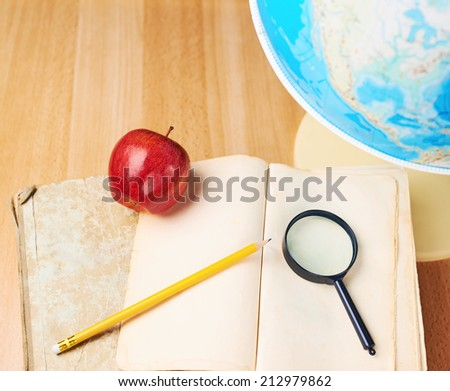 Studying geography composition of the red apple, old books, globe and magnifying glass against the wooden desk background - stock photo