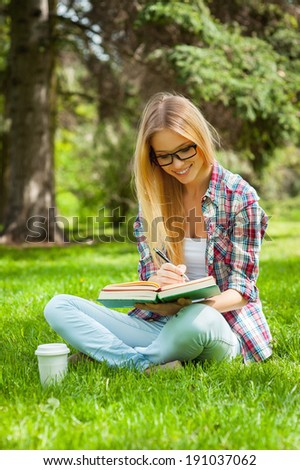 Studying outdoors. Confident young female student studying while sitting in a park - stock photo