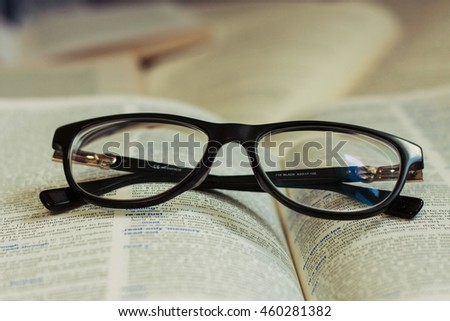 Studying: stylish black reading glasses on the dictionary page