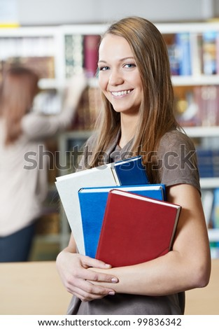 Studying young college student girl in a library with education books - stock photo