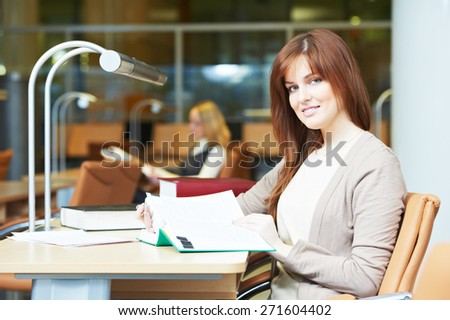 Studying young teenage college student girl  in a library with books - stock photo