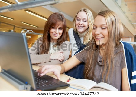 Studying young teenage college student girl in a library with Laptop computer - stock photo