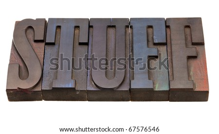stuff  word in antique wooden letterpress printing blocks, stained by color inks, isolated on white