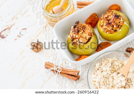 Stuffed apples with oat, raisins, walnuts, dried apricots, cinnamon and honey in white form, white wood background, top view - stock photo