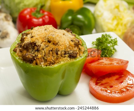 """stuffed bell pepper with beef and rice topped with parmesan cheese and garnished with sliced tomatoes and parsley""""stuffed peppers"""" - stock photo"""