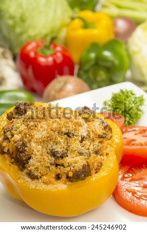 """stuffed bell pepper with beef and rice topped with parmesan cheese and garnished with sliced tomatoes and parsley""""stuffed bell peppers"""" - stock photo"""