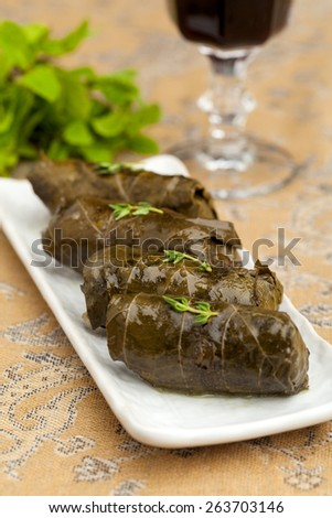 stuffed cabbage rolls in grape leaves on a decorated table closeup - stock photo